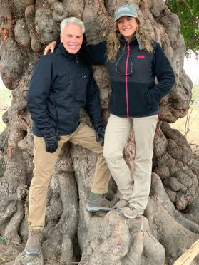 man and woman stand in front of large tree